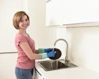 Sorriso vermelho bonito da mulher do cabelo feliz e positivo que lava os pratos na banca da cozinha Imagens de Stock Royalty Free