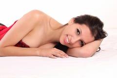 Sorriso vermelho de reclinação do espartilho da mulher caucasiano nova Foto de Stock Royalty Free