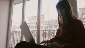 Sorrisos adultos novos bonitos felizes da mulher de negócios usando o portátil na janela do apartamento no verão Paris, trem que  filme