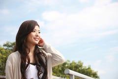 Sorrisos asiáticos novos da mulher Imagens de Stock