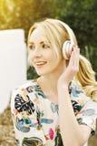 Sorrisos caucasianos novos da menina ao escutar a música nos fones de ouvido inspirados olhando afastado a luz morna foto de stock