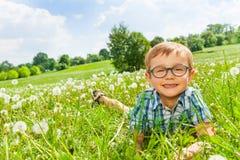 Sorrisos do rapaz pequeno que colocam em uma grama fotos de stock