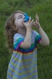 Sorrisos e jogos da criança pequena com o girador no fundo da grama verde Foto de Stock