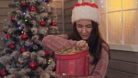 Sorrisos felizes da menina com presente do Natal à disposição A moça abre o presente do Natal video estoque