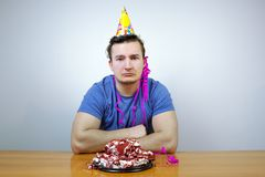 Sorrorful man with birthday party cone hat on head and crumple cake,  crying. guy in bad mood while having celebration stock image
