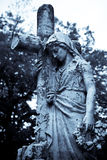 Sorrow. A girl statue grieving at the cross Royalty Free Stock Photos