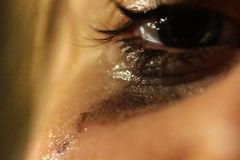 Sorrow. Closeup of a crying eye, a victim of bullying Royalty Free Stock Images