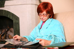 Sorrow senior woman at home holding a photoes. Sorrow senior woman at home holding a group of photos Stock Images