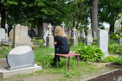 Sorrow woman shrinked near father husband tomb. In cemetery Royalty Free Stock Photo