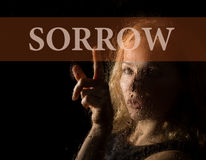 Sorrow written on virtual screen. hand of young woman melancholy and sad at the window in the rain. Sorrow written on virtual screen. hand of young woman Royalty Free Stock Photo