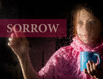 Sorrow written on virtual screen. young woman melancholy and sad at the window in the rain, she holding a cup of hot Stock Image