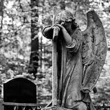 The Sorrowful Angel. Weeping angel with a cross, space for text. The Sorrowful Angel. The tomb of the 19th century, the German introduced city of Moscow.Weeping royalty free stock photos