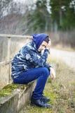 Sorrowful boy on the bridge near road royalty free stock images