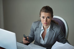 Sorrowful business woman working at desk. Sorrowful business woman working at hotel room royalty free stock image