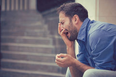 Sorrowful crying man sitting on steps outdoors. Sorrowful crying young man sitting on steps outdoors Royalty Free Stock Images