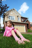 Sorrowful girl sits on grass near cottage. Sorrowful girl sits on green grass near cottage and looks into distance Stock Image