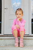 Sorrowful girl sits on stairs near door. Little sorrowful girl sits on stairs near white door and thinks Royalty Free Stock Photos
