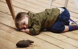 Sorrowful little boy on floor Stock Photos