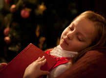 Sorrowful little girl near Christmas tree. Little girl near Christmas tree reading book Stock Image