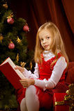Sorrowful little girl near Christmas tree. Little girl near Christmas tree reading book Royalty Free Stock Photos