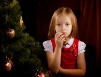 Sorrowful little girl near Christmas tree Stock Photography