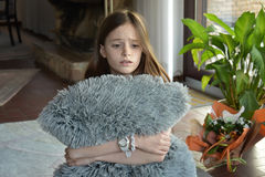 Sorrowful looking girl. Sorrowful looking teenager girl sitting on the floor, cuddling with a pillow Royalty Free Stock Images