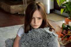 Sorrowful looking girl. Sorrowful looking teenager girl sitting on the floor, cuddling with a pillow Stock Photo