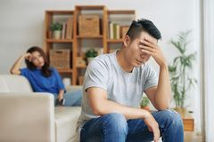 Sorrowful man covering eyes after conflict with woman. Upset Asian men sitting in living room with women on background and covering eyes in depression having Stock Photography