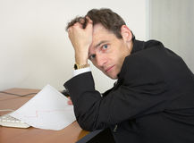 Sorrowful man at the office, on a workplace Stock Image