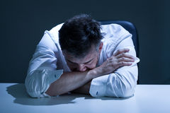 Sorrowful man sitting at the table Royalty Free Stock Photography