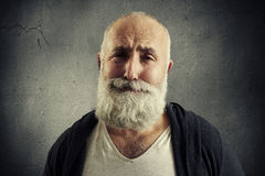 Sorrowful senior man with grey-haired beard. Over dark background royalty free stock photography