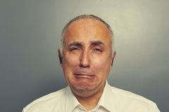 Sorrowful senior man over grey background. Portrait of sorrowful senior man over grey background Royalty Free Stock Photos
