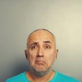 Sorrowful senior man over grey. Portrait of sorrowful senior man over grey background Royalty Free Stock Images