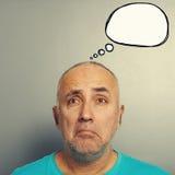Sorrowful senior man with white speech balloon Stock Photos