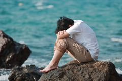 Sorrowful stressed Asian man sit and hug knees up to the chest at the rock of seashore. Sorrowful stressed Asian man sit and hug knees up to the chest at the Royalty Free Stock Photos