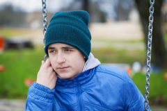 Sorrowful teenage boy. Swinging in the park Stock Photography