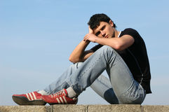Sorrowful Teenager. Young male model sitting on the stone blocks royalty free stock photos