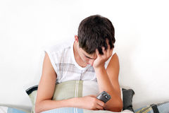 Sorrowful Teenager get SMS. Sad Teenager sitting with pillow and mobile phone on the Bed in Home interior stock image