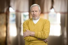 Sorrowful tragic old man portrait. Sad frustrated senior grandpa in yellow sweater with folded arms. Blurred room background Royalty Free Stock Photos