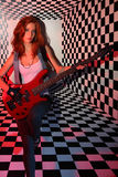 Sorrowful woman plays electric guitar in studio. Sorrowful woman plays red electric guitar in studio with checkered background in red light Stock Photography