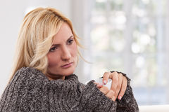 Sorrowful woman with an white-colored cup Royalty Free Stock Image
