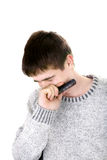 Sorrowful young man. With mobile phone on the white background Stock Images