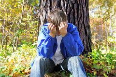 Sorrowful young man. Sorrowful teenager sitting in the autumn forest alone royalty free stock photo