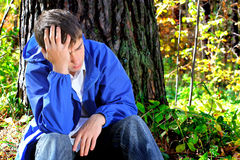 Sorrowful young man. Sorrowful teenager sitting in the autumn forest alone royalty free stock photography