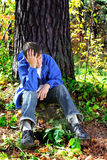 Sorrowful young man. Sorrowful teenager sitting in the autumn forest alone stock images
