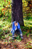 Sorrowful young man. Sorrowful teenager sitting in the autumn forest alone royalty free stock images