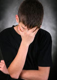 Sorrowful Young Man. Sad Young Man On the Black Background hide his Face stock photos