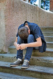 Sorrowful Young Man. Sad Young Man on the landing Steps of the Old House Royalty Free Stock Photo