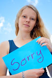 Sorry. Young lady shows shield: Sorry royalty free stock images