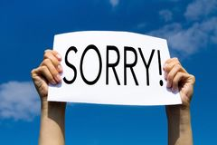 Sorry, apologise concept. Sorry, concept, hands holding sign in blue sky royalty free stock photo